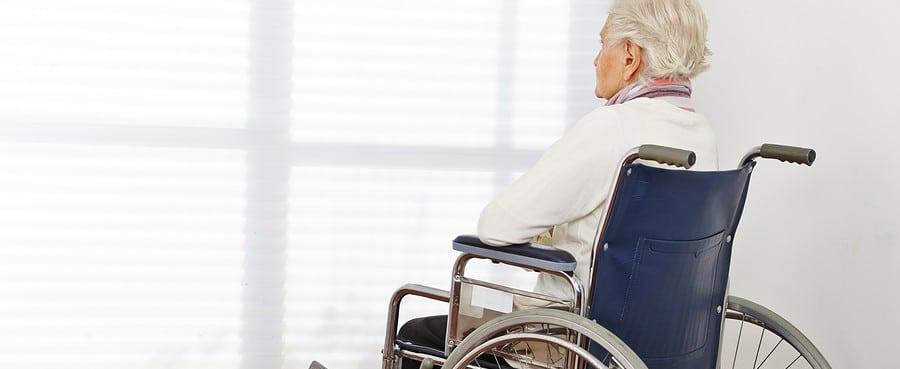 senior woman in wheelchair looking toward shaded window